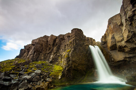 Scenic view of waterfall falling from cliff against sky