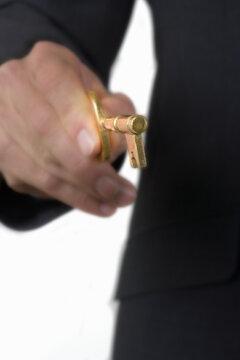 Close up of businessman holding an antique brass skeleton key.