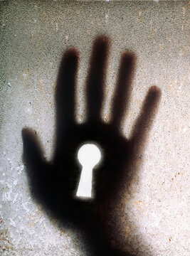 Keyhole in palm of a silhouetted hand