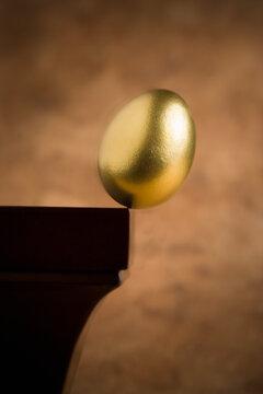 Golden egg balance on shelf.