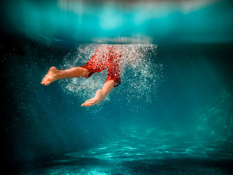 Underwater picture of a boy swimming in a pool