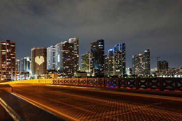 Miami, sunset panorama with colorful illuminated business and residential buildings and bridge on...