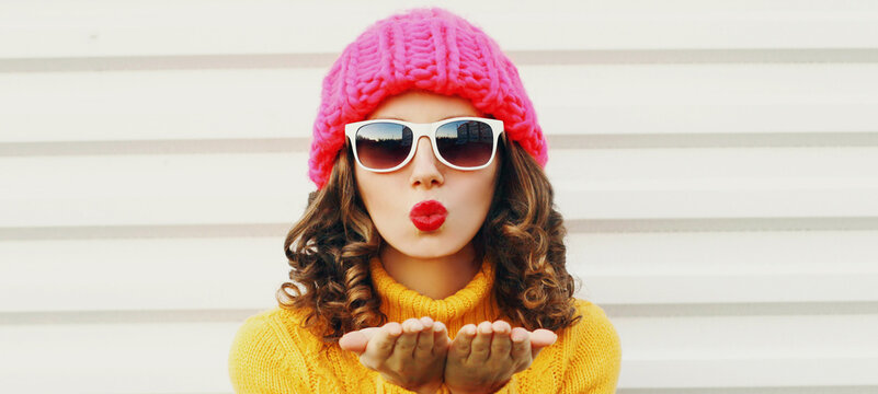 Winter portrait close up of young woman blowing red lips sending sweet air kiss wearing a pink hat, yellow sweater over white background