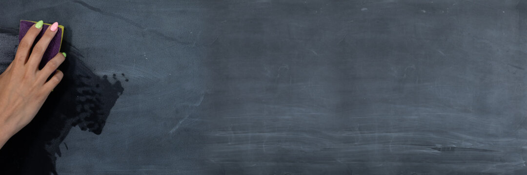 Panoramic frame for a woman's hand wiping the blackboard with a wet sponge before the next lessons in the classroom. Prepares a place for writing on a school blackboard.