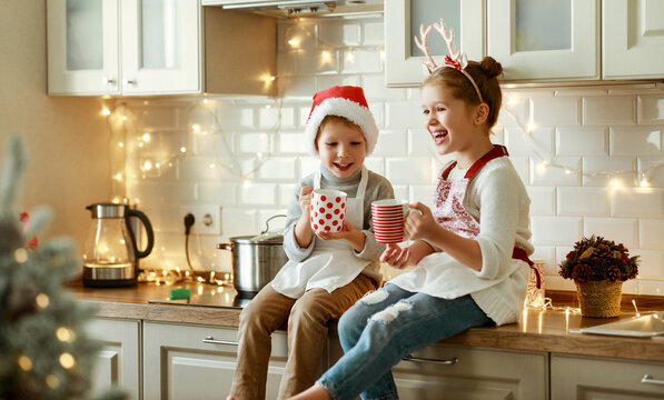 happy children on Christmas eve,   girl and boy drink hot cocoa drink that they baked together in cozy kitchen at home.