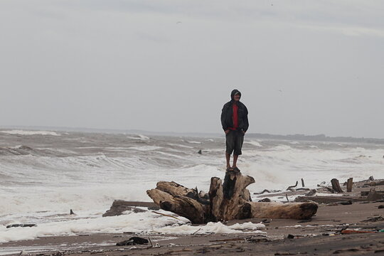 A man stands on a trunk of a tree as Storm Iota approaches, in Cedeno