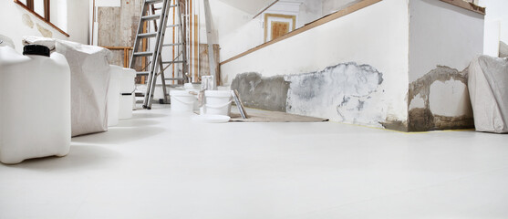 Obraz Low angle of indoor shot of construction or building site of home renovation with tools with paint buckets and primer jerry can on white floor with copy space - fototapety do salonu