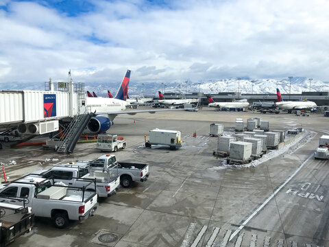 View of the SLC airport tarmac with vehicles and Delta airplanes.