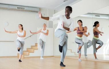 Portrait of dancing African-American practicing vigorous swing during group training in dance studio.