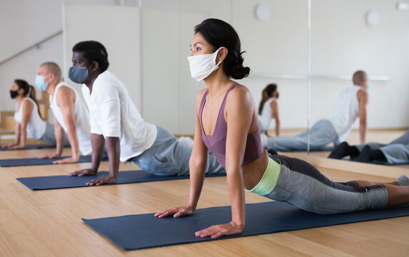 Young woman in face mask for viral protection practicing yoga at group class