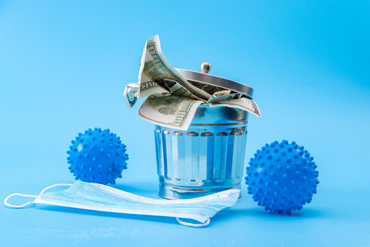 Economic impact of the coronavirus epidemic and failed cost-benefit analysis of covid-19 concept with virus, masks and trashcan filled with dollars going to waste isolated on blue background