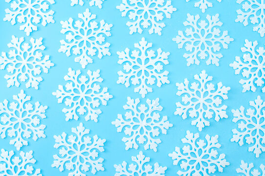 Christmas wallpaper and winter pattern concept with repeating snowflakes with every snowflake in different position isolated on pastel blue background
