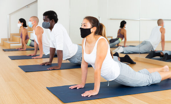 Adult women and men wearing protective masks performing yoga exercises during group workout in gym. Healthy lifestyle and pandemic precautions concept.