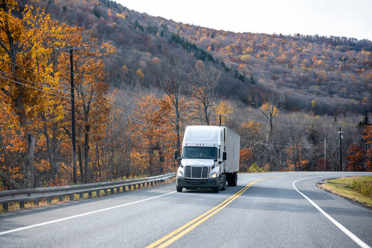 Powerful big rig semi truck with refrigerator semi trailer transporting cargo running on the winding autumn road in Massachusetts New England mountain