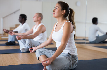 Portrait of young woman sitting in lotus position practicing meditation during group yoga class