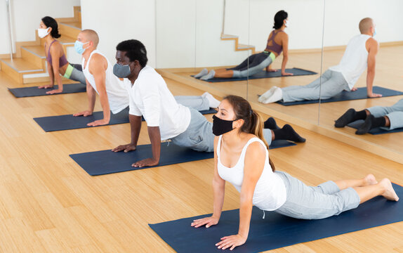 Multiethnic group of sporty people wearing protective masks to prevent viral infections, practicing yoga poses while exercising at fitness center