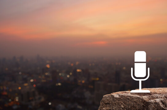 Microphone flat icon on rock mountain over blur of cityscape on warm light sundown, Business communication concept