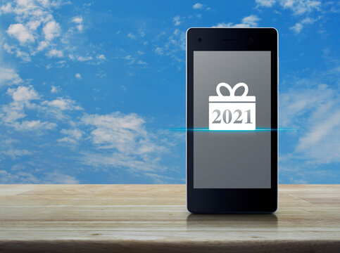 Gift box happy new year 2021 flat icon on modern smart mobile phone screen on wooden table over blue sky with white clouds, Business happy new year 2021 shop online concept