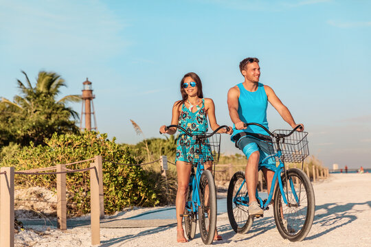 Biking activity couple tourists having fun doing outdoor sport on Florida beach vacation with rental bikes on Sanibel Island by the Lighthouse. woman with man friend riding bicycles outdoor lifestyle.
