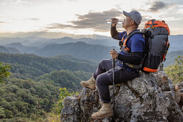 Hiker with backpack relaxing on top of the mountain and drinking bottled water