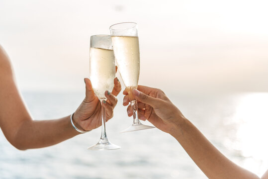 Hand holding a glass drinking wine on Sunset sea background.
