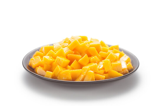 Diced mango in a black plate on white background.
