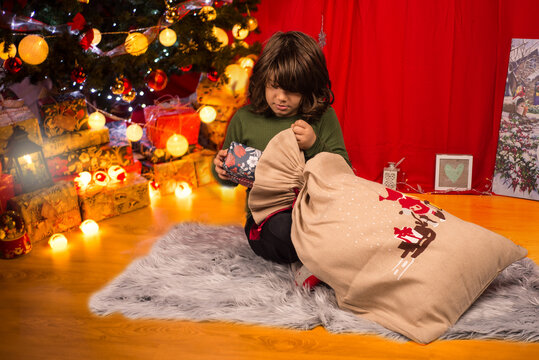 Boy taking a Christmas gift from bag
