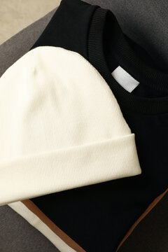 Pile of sweatshirts and white beanie on chair