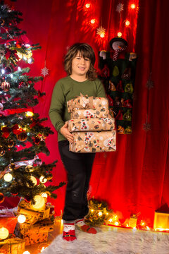 Happy kid boy holding Christmas presents