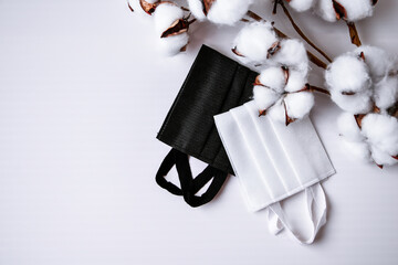 Cotton plant flower with protective medical white face mask on white background. Surgical mask, medical mask Fototapete