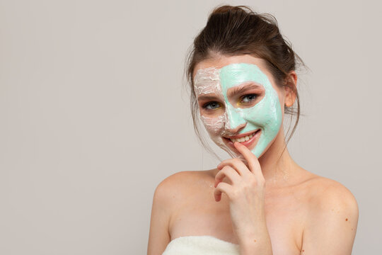 young woman with cream on her face. skin care. Gray background