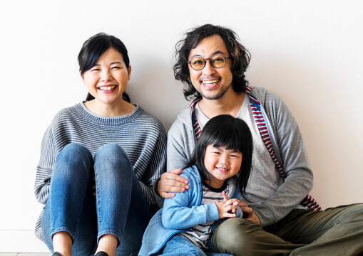 Smiling Japanese family with a daughter sitting on the floor