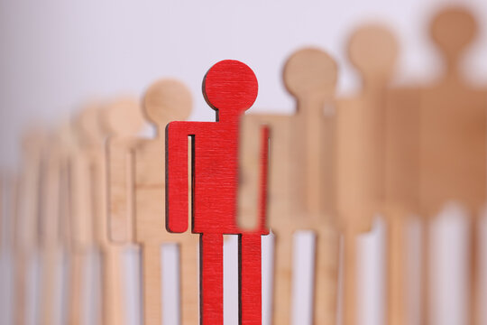 Among group of wooden toy men there is one red in line closeup. Observance of distance for prevention of infection with covid- 19 concept