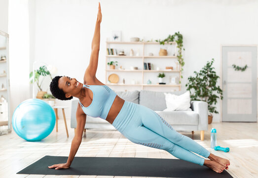 Home fitness concept. Determined black woman working out on sports mat indoors, doing side plank exercise