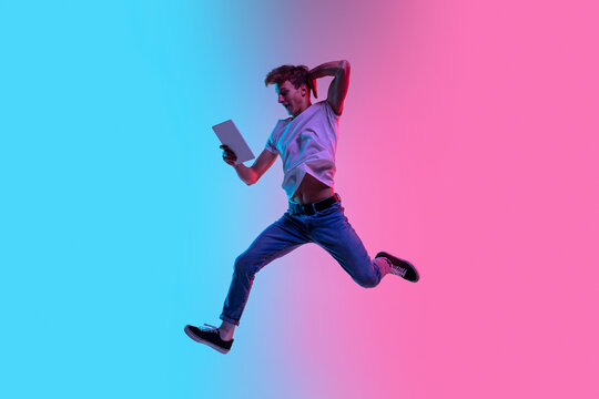 Winner with tablet. Young caucasian man's jumping high on gradient blue-pink studio background in neon light. Concept of youth, human emotions, facial expression, sales, ad. Beautiful model in casual.