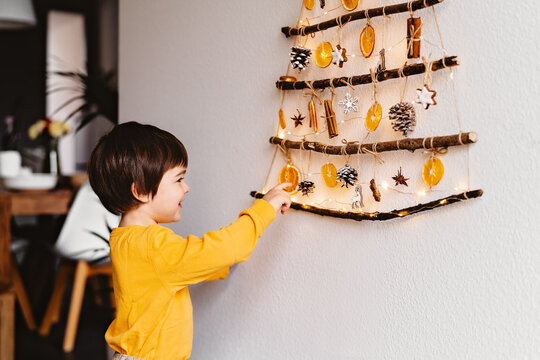 Little child laying with handmade craft Christmas tree made from sticks and natural materials hanging on wall. Sustainable Christmas, zero waste, plastic free, eco friendly.