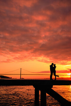 Silhouette of lovers kissing with a  bridge in the background sunset time Lisbon