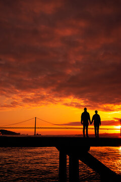 Silhouette of couple holding hands  a  bridge in the background sunset time, Lisbon