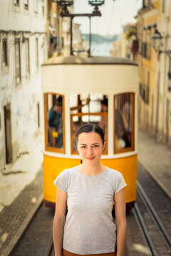 Young smiling woman tourist standing near the  retro yellow tram on the street in Lisbon city, Portugal