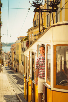 Young smiling man tourist standing in the  retro yellow tram on the street in Lisbon city, Portugal