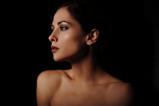 Beautiful mysterious woman in darkness with healthy neck, shoulders and golden health skin in shadows on dramatic  black background with empty copy space. Closeup portrait. Art.