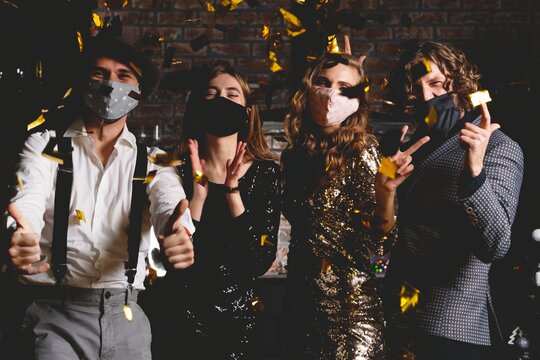 Enjoying amazing party. Corona virus pandemic. Group of beautiful young people in protective medical mask dancing, looking happy