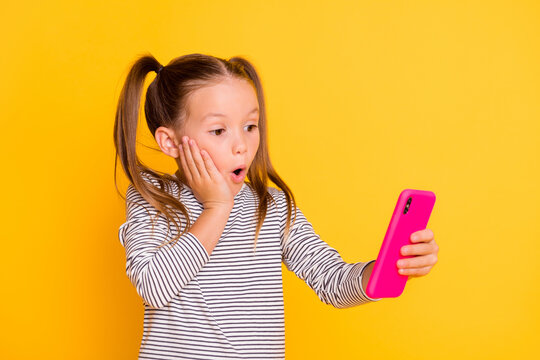 Photo of young shocked impressed little girl kid child hold smartphone cellphone isolated on yellow color background