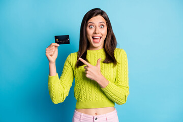 Photo of young girl show gesture finger bank card ad promo advice choose wear green jumper isolated over blue color background