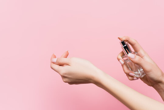 cropped view of woman holding bottle with luxury perfume isolated on pink