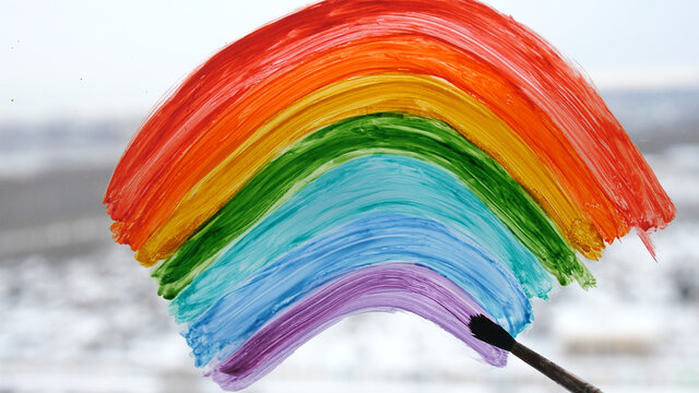 a woman's hand painting rainbow during Covid-19 quarantine at home. Stay at home Social media campaign for coronavirus prevention, let's all be well, hope during coronavirus pandemic concept
