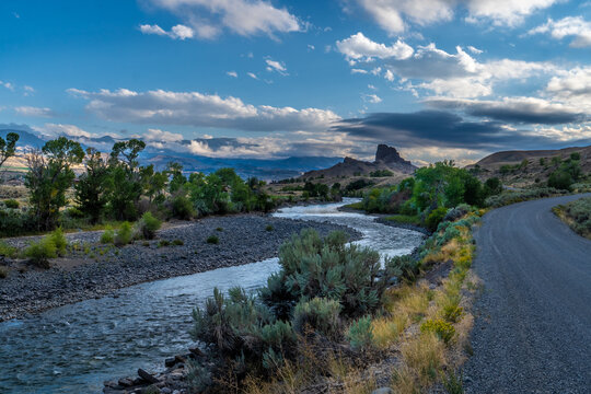 Butte and river under dramatic clouds with distance mountains and trees and shrub in the foreground, Castle Rock, South Fork Shoshone River, Cody, Wyoming