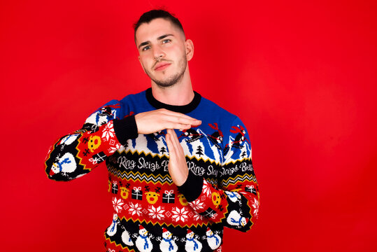 Young handsome Caucasian man wearing Christmas sweater against red wall, being upset showing a timeout gesture, needs stop, asks time for rest after hard work, demonstrates break hand sign