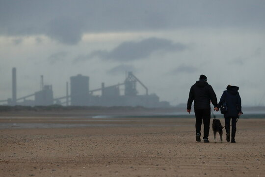 People walk on the beach as industries are seen in the background in Teesside