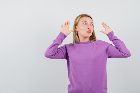 cute blond lady showing surrender gesture, pouting lips, looking up in purple sweater and looking confused. front view.